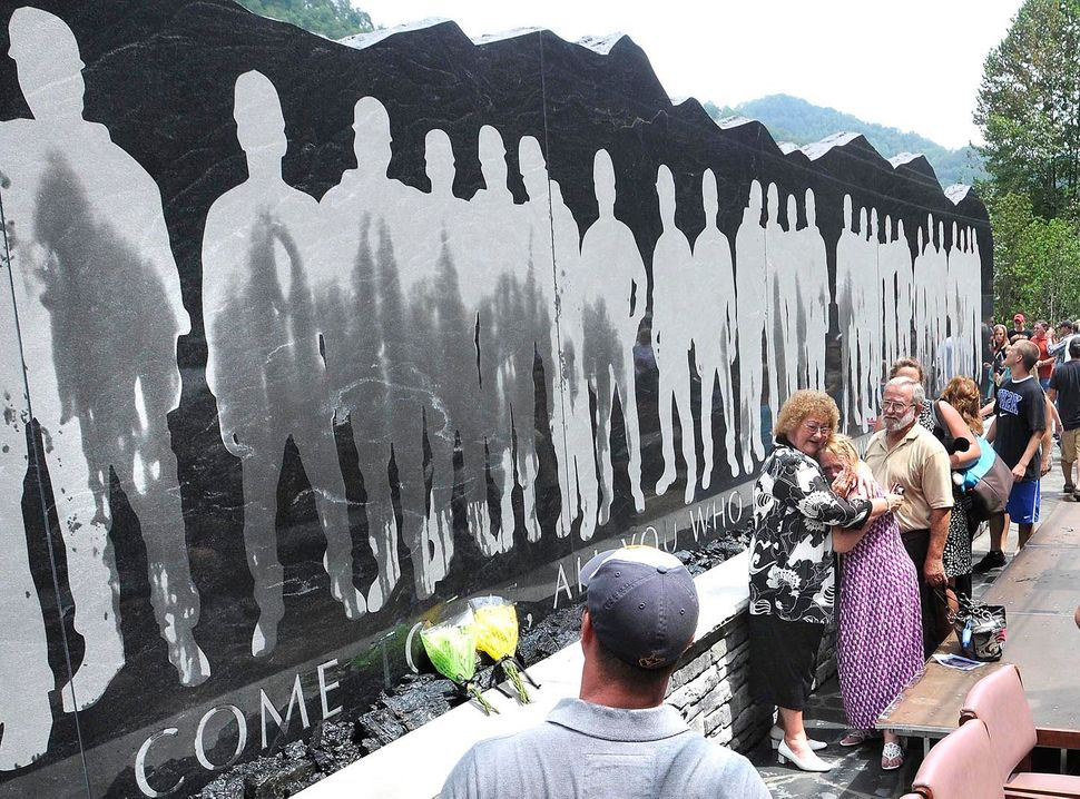 Family and friends view the 48-foot-long granite Upper Big Branch Miners monument, Friday, July 27, 2012 in Whitesville, W.Va