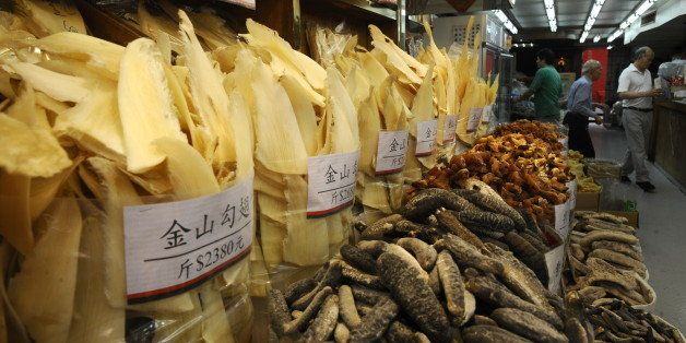 People shop as shark fins (L) are displayed for sale in Hong Kong's Shueng Wan district on March 21, 2010. China, Japan and R