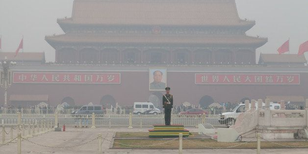 BEIJING, CHINA - MARCH 27:  Security personnel stand guard at Tiananmen Square blanketed in smog on March 27, 2014 in Beijing