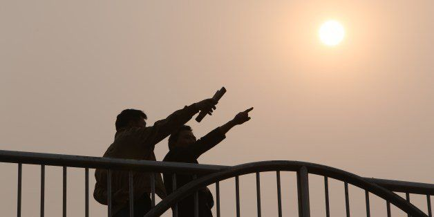 This picture taken on March 26, 2014 shows residents talking to each other on a bridge in Beijing as environmental authoritie