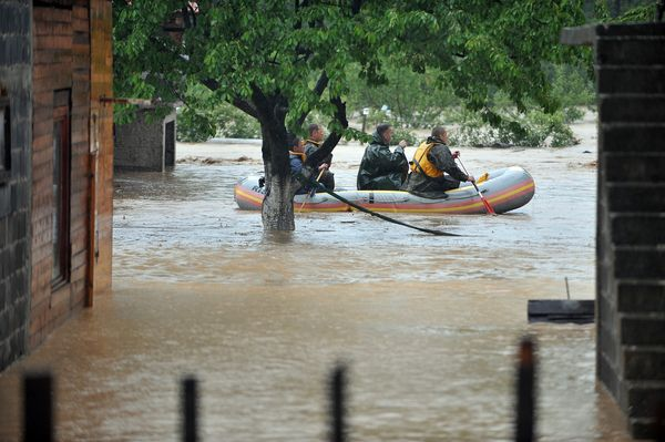 Members of the Bosnian armed forces use an inflatable boat during an operation to evacuate residents from homes surrounded by