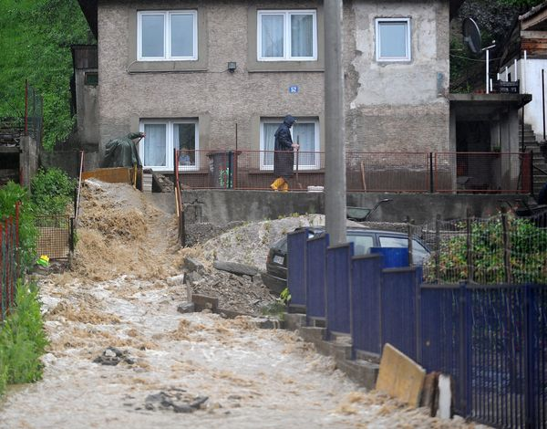 Men attempt to redirect a torrent of floodwater to protect a home in the village of Topcic Polje, near the central Bosnian to