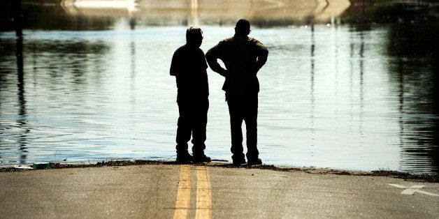 GREELEY, CO - JUNE 03: Two men stand at the edge of the flood water as it continues to rise along the Poudre River in Greeley