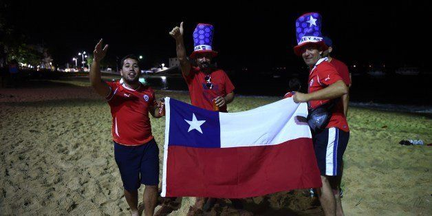 Fans of Chile celebrate on the beach in Salvador De Bahia on June 18, 2014  after the Group B football match between Spain an