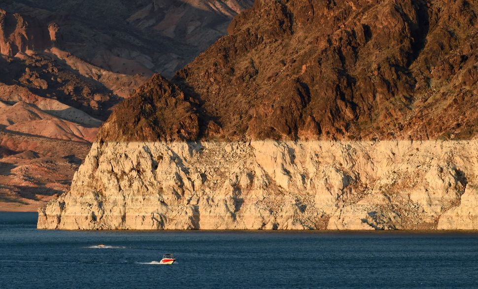 """Boaters near Horsepower Cove pass in front of a white """"bathtub ring"""" on the rocks on July 13, 2014 in the Lake Mead National"""