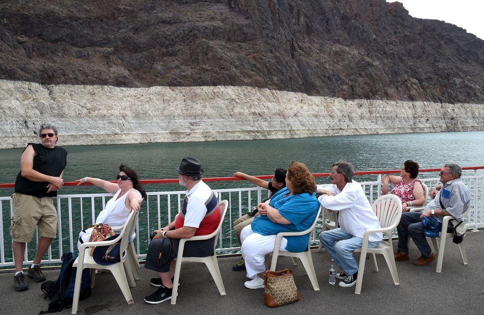 Passengers taking a boat tour pass in front of a mineral-stained rock wall on July 14, 2014 in the Lake Mead National Recreat