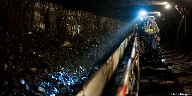 A coal miner shines his head lamp on coal transported on a conveyor belt after being sheared off the wall during longwall min