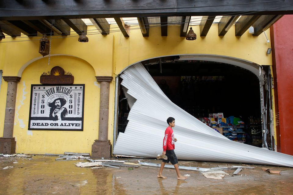 A kid walks by a souvenir store damaged by Hurricane Odile on San Lucas' main street, in Los Cabos, Mexico, Monday, Sept. 15,