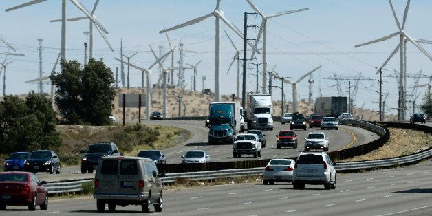 PALM SPRINGS, CA - MARCH 27:  Automobiles pass by giant wind turbines powered by strong winds on March 27, 2013 in Palm Sprin