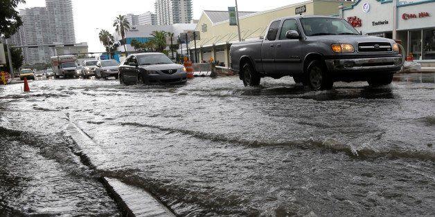 Vehicles negotiate heavily flooded streets as rain falls, Tuesday, Sept. 23, 2014, in Miami Beach, Fla. Certain neighborhoods