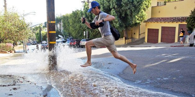 A man leaps over water flooding a side street after a water main break sent churning, muddy water down Sunset Boulevard and h