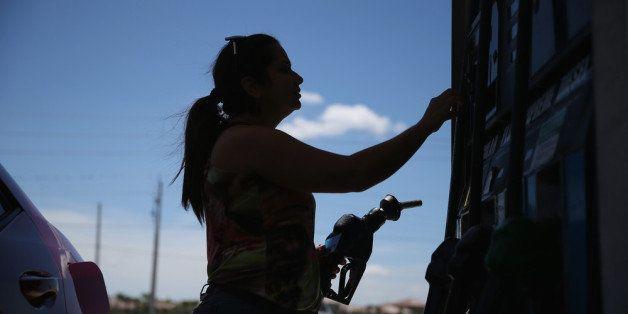 PEMBROKE PINES, FL - APRIL 21:  Dora Galeano pumps gas at the Victory gas station on April 21, 2014 in Pembroke Pines, Florid
