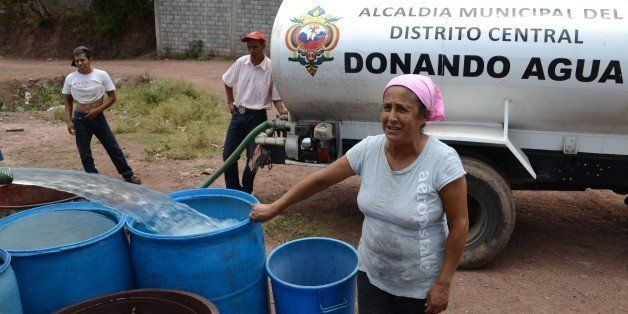 A tanker fills containers with water in a poor neighbourhood on the outskirts of Tegucigalpa on August 7, 2014. Honduras and