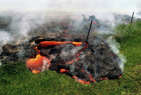 This Oct. 25, 2014 photo provided by the U.S. Geological Survey shows lava flow advancing across the pasture between the Paho