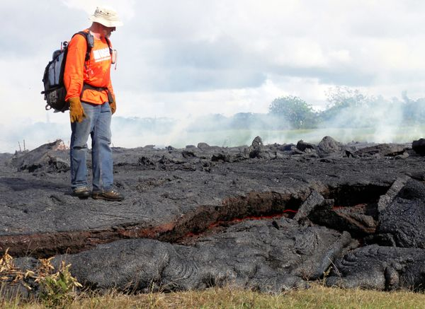 This Oct. 25, 2014 photo provided by the U.S. Geological Survey shows a Hawaii Volcano Observatory geologist standing on a pa