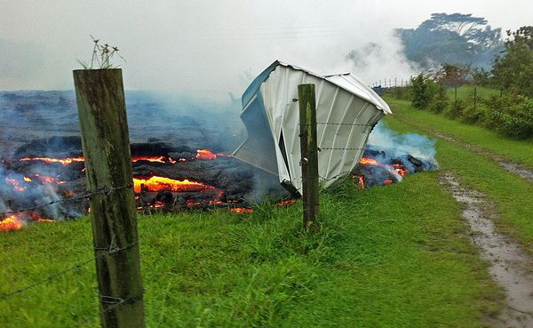 This Oct. 25, 2014 photo provided by the U.S. Geological Survey shows a small shed being consumed by lava in a pasture betwee