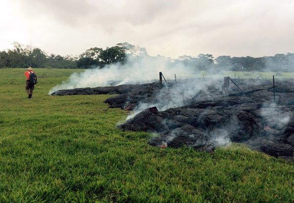 This Oct. 26, 2014 photo provided by the U.S. Geological Survey a Hawaii Volcano Observatory geologist mapping the margin of