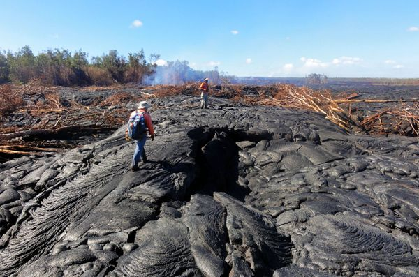 In this Oct. 22, 2014 photo provided by the United States Geological Survey, Hawaii Volcano Observatory geologists walk over