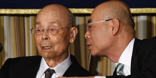 Top Japanese sushi chef Jiro Ono (L) listens to his son, Yoshikazu Ono (R), while attending a press conference at the Foreign