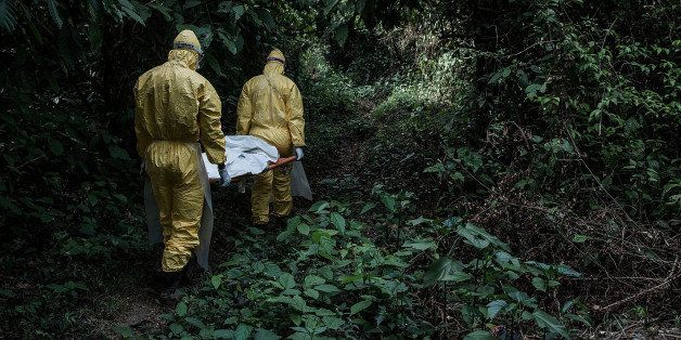 BO DISTRICT, SIERRA LEONE - MARCH 05:  Healthcare workers in protective equipment bury a 13-year-old boy dying of Lassa fever