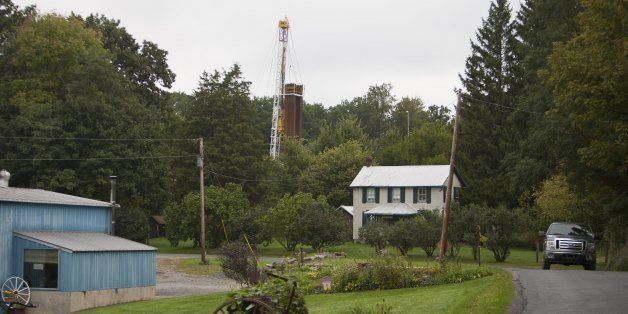CALVERT, PA - SEPTEMBER 9: A car drives by a home with a nearby derrick drilling for natural gas near Calvert, Pennsylvania.