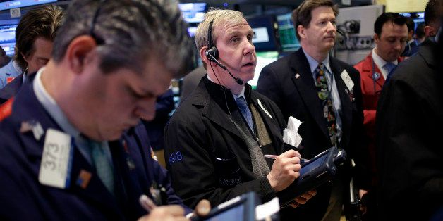 Traders work on the floor at the New York Stock Exchange in New York, Monday, April 22, 2013.  Stocks edged lower on Wall Str