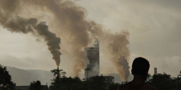 A man stands in front of a chemical factory as it discharges exhaust into the air of Mumbai, India, on Monday, Sept. 13, 2010