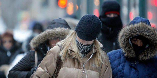 FILE- In this Jan. 28, 2014, file photo, morning commuters bundle up in Chicago. Meteorologists are confidently forecasting f