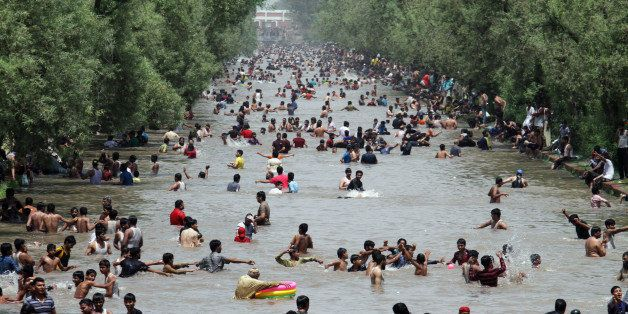 People cool themselves off in a canal in Lahore, Pakistan, where temperature reached 46 degrees Celsius (104 Fahrenheit) on S