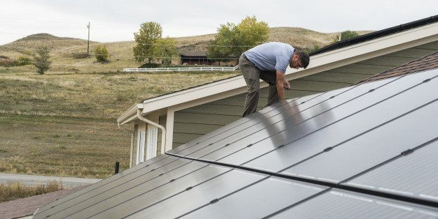GOLDEN, CO - October 15: Joe Ostrowski cleans up around the side of one of the newly installed solar panels Wednesday, Octobe