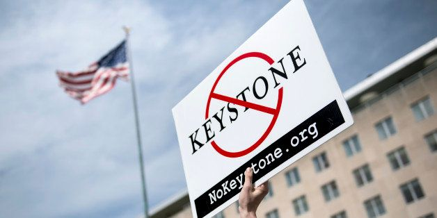 An activist holds up a sign outside the State Department during a protest of the Keystone XL pipeline on March 7, 2014 in Was