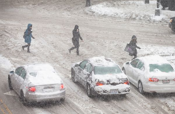 Pedestrians and motorists navigate a snow-covered street on February 1, 2015 in Chicago, Illinois. (Photo by Scott Olson/Gett