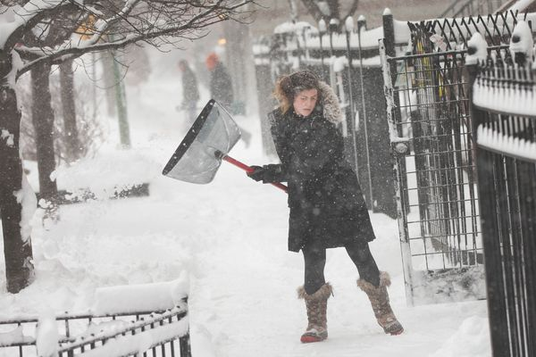 Aryn Sothbarr clears snow from the sidewalk outside her home on February 1, 2015 in Chicago, Illinois. (Photo by Scott Olson/
