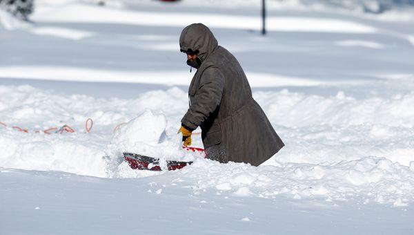 A homeowner shovels snow in Detroit, Monday, Feb. 2, 2015. (AP Photo/Paul Sancya)