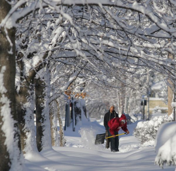 Two men clear snow from a sidewalk Monday, Feb. 2, 2015, in Blue Island, Ill. (AP Photo/M. Spencer Green)