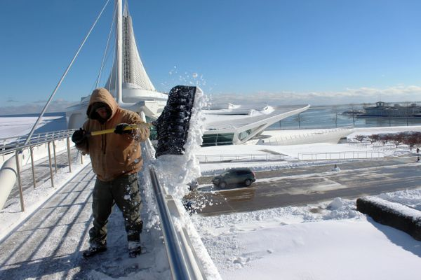 Jose Robles clears snow from a bridge at the Milwaukee Art Museum Monday, Feb. 2, 2015 in Milwaukee. (AP Photo/Carrie Antlfin