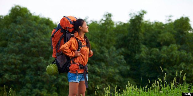 young woman carrying big backpack and enjoy the beauty of the nature