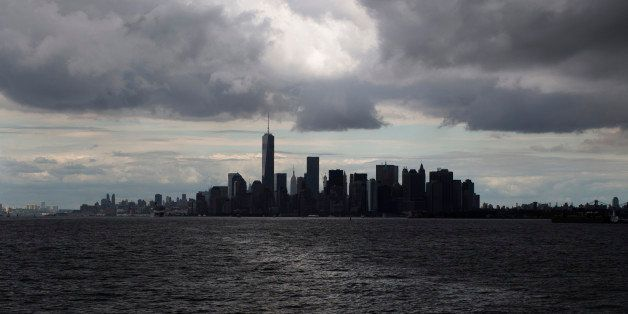 Rain clouds gather over the lower Manhattan skyline, Saturday, Aug. 23, 2014, in New York. (AP Photo/John Minchillo)