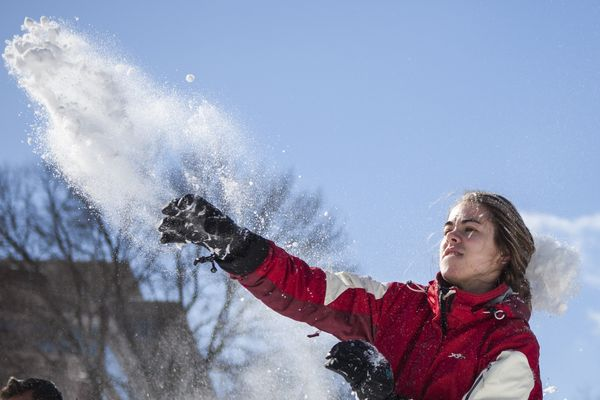 A woman throws a snowball from the fountain as hundreds of people gather for a massive snowball fight at Dupont Circle in Wa
