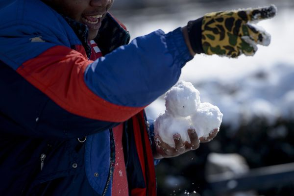 A man gets ready to throw snowballs in Dupont Circle February 17, 2015 in Washington, DC. T