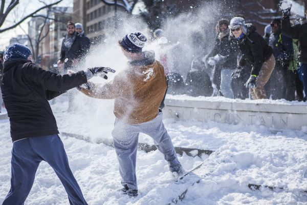 A man gets pelted with snowballs while trying to assault the inner fountain as hundreds of people gather for a massive snowb