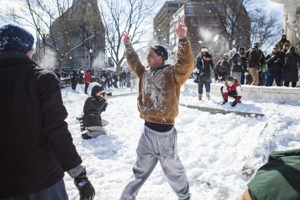 A man raises his arms in surrender after getting pelted with snowballs while trying to assault the inner fountain as hundreds