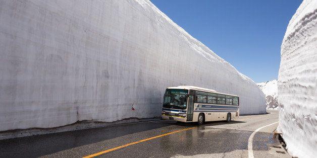 [UNVERIFIED CONTENT] Bus crossing the snow walls of the Murodo Snow Corridor along the Tateyama Kurobe Alpine Route.