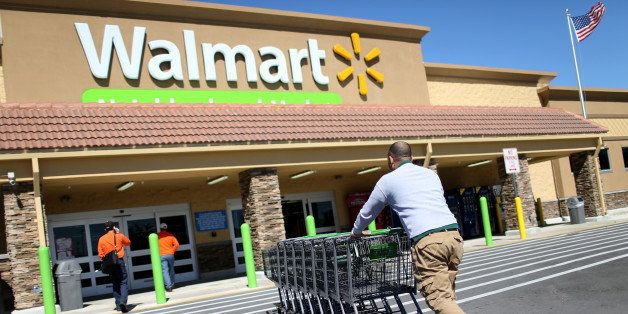 MIAMI, FL - FEBRUARY 19:  Walmart employee Yurdin Velazquez pushes grocery carts at a Walmart store on February 19, 2015 in M