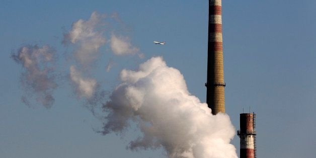 FILE - In this Nov. 13, 2014 file photo, a passenger airliner flies past steams emitted from a coal-fired power plant in Beij