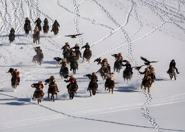 Chinese Kazakh eagle hunters ride with their eagles during a local competition in the mountains of Qinghe County, China, on J
