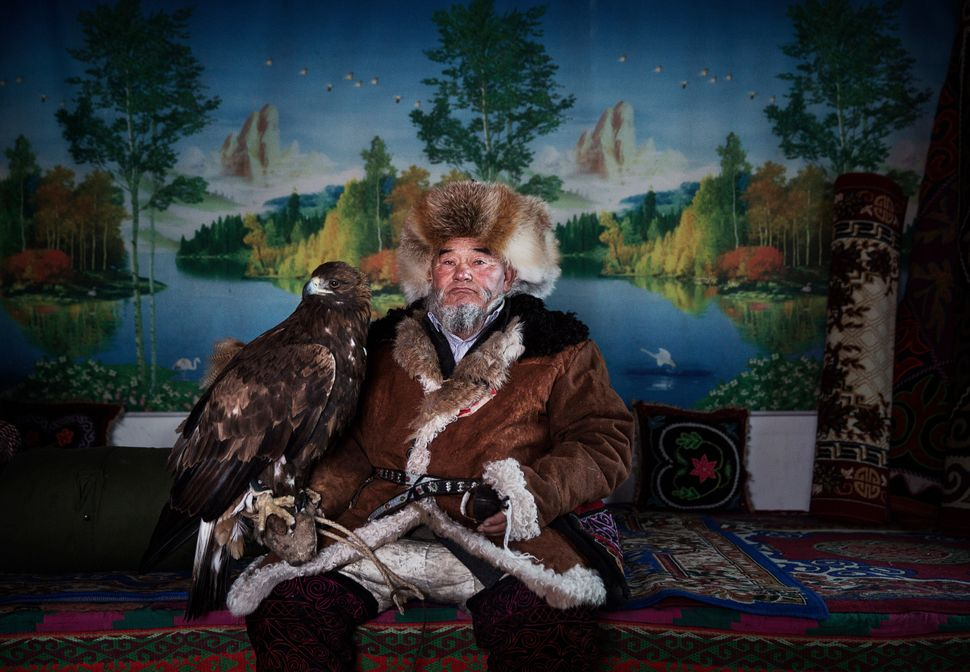 Chinese Kazakh eagle hunter Margars Mazkin, 74, sits with his eagle before leaving for a competition in the mountains of Qing