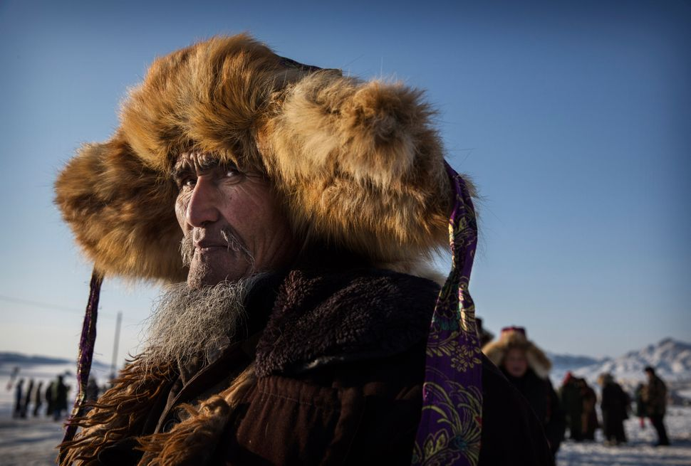 A Chinese Kazakh horseman watches at an eagle hunting competition in the mountains of Qinghe County, China, on Jan. 31, 2015.