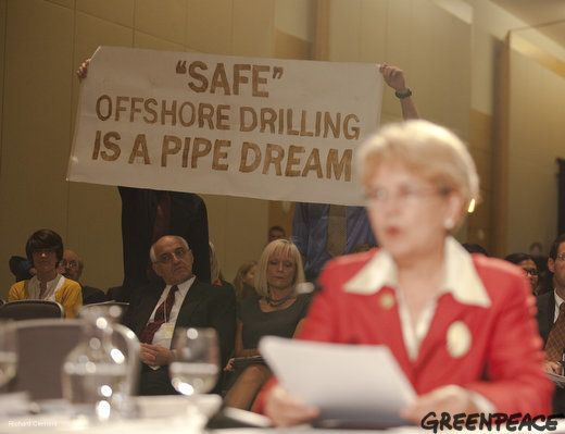 Greenpeace activists displayed a banner painted in oil from the Gulf coast oil spill as NOAA Administrator Jane Lubchenco add