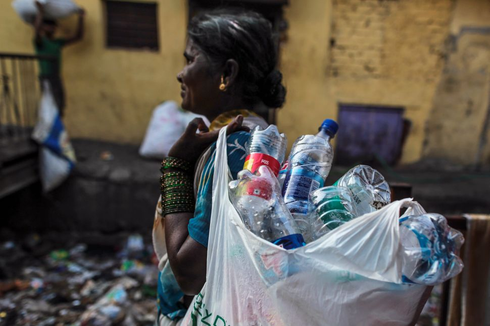 A rag picker carries a bag of collected plastic bottles in the Govandi area of Mumbai, India, on Wednesday, March 11, 2015.